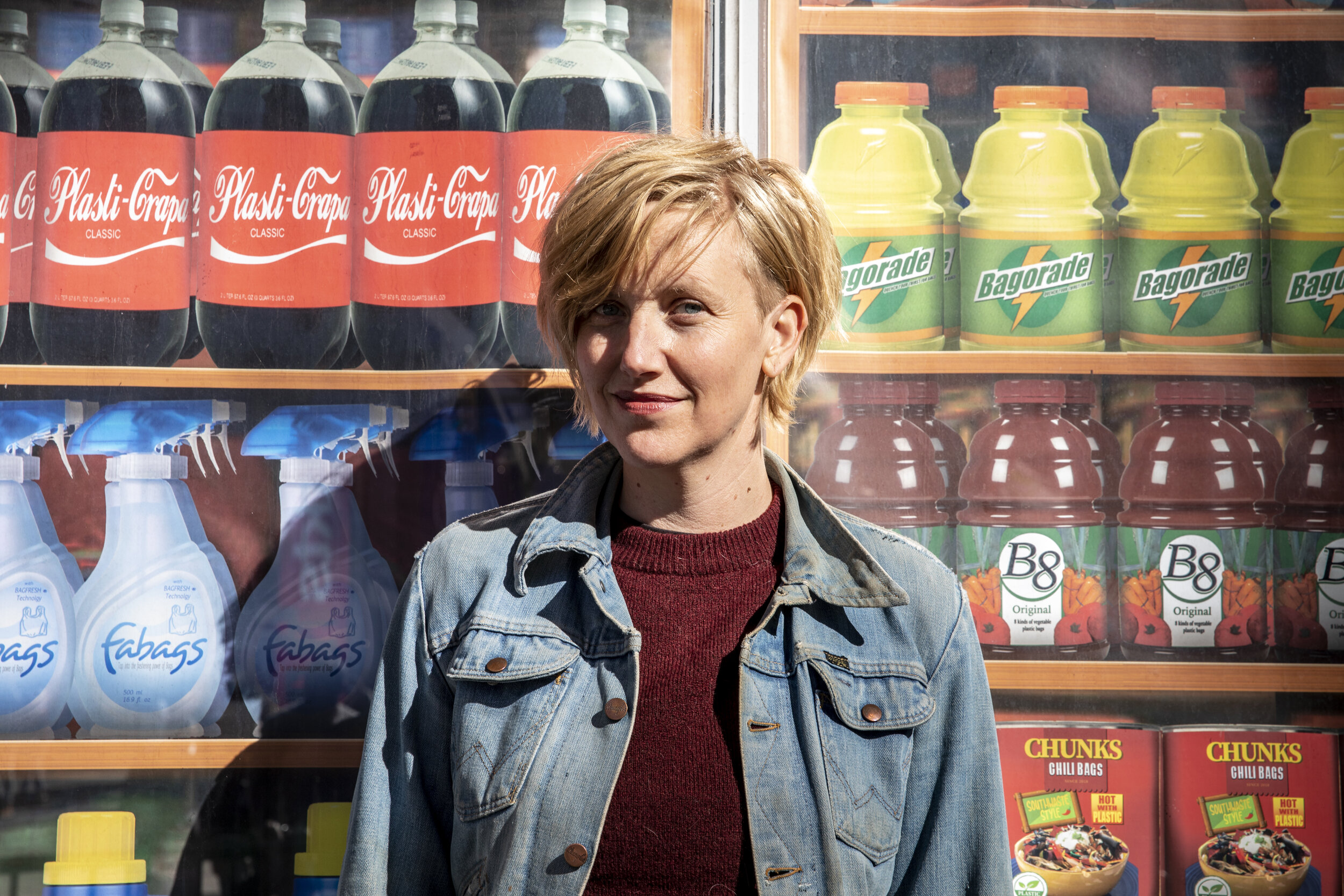 Artist Robin Frohardt stands in front of grocery store items made out of plastic bags from one of her exhibits
