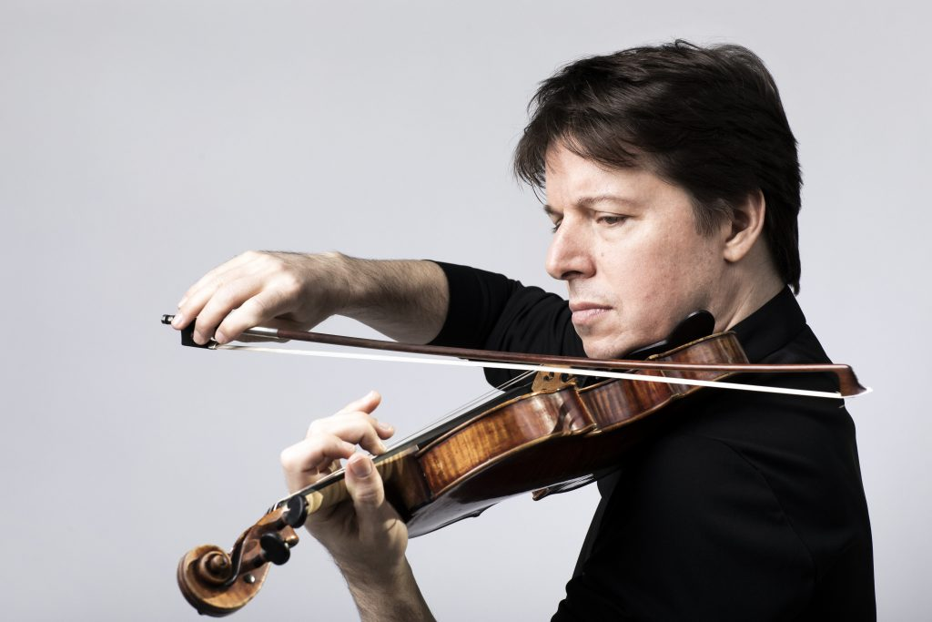 Violinist Joshua Bell holds a violin under his chin, playing the instrument with a pensive look on his face.