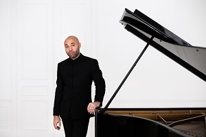 Aaron Diehl, a Black man wearing a black suit, stands beside his grand piano.