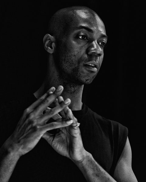 Dancer Shamel Pitts, a Black man, clasps his hands and looks away from the camera.