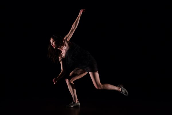 Michelle Dorrance, a white woman wearing a black leotard, tap dances on a darkly lit stage.
