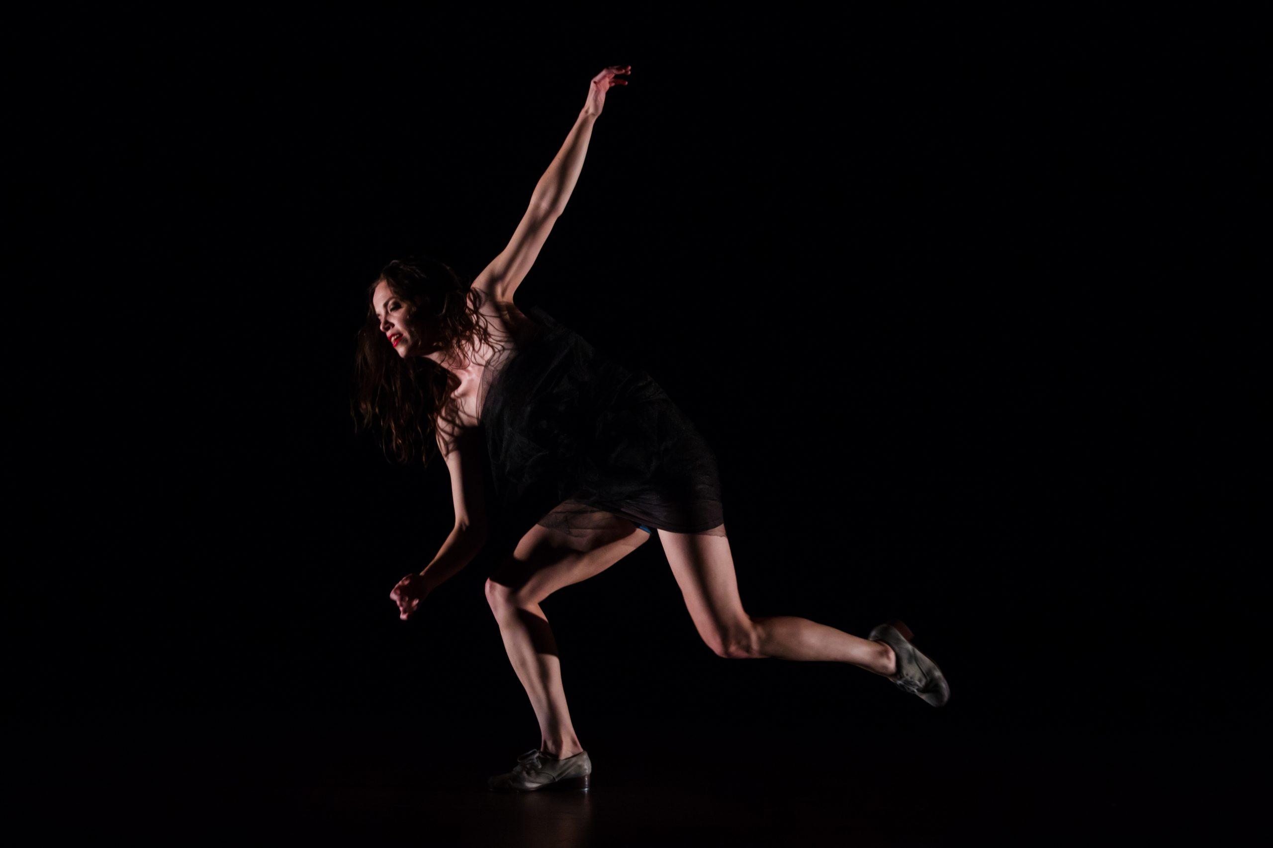 Michelle Dorrance, a white woman wearing a black leotard, tap dances on a darkly lit stage.