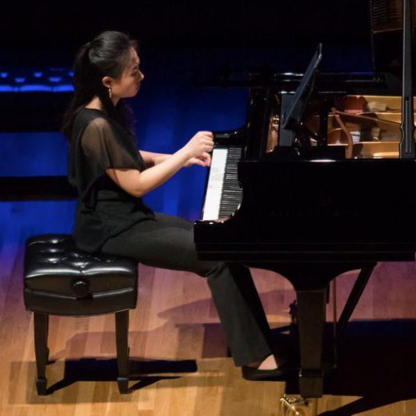 Clara Yang, an Asian women wearing black pants and a sheer black top, plays a grand piano.