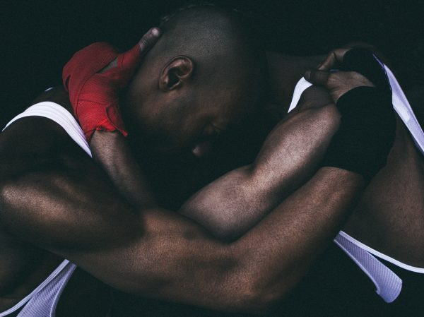 two Black men in white sleeveless shirts locked in embrace at the neck