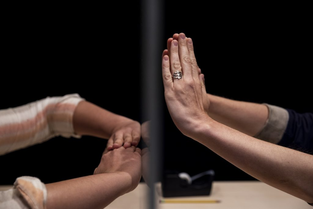 Two people reach their hands across a table, separated by glass.