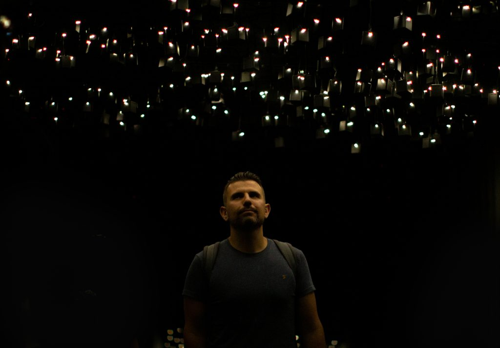 A man stands beneath hundreds of teardrop-shaped lights and speakers at Atmospheric Memory.