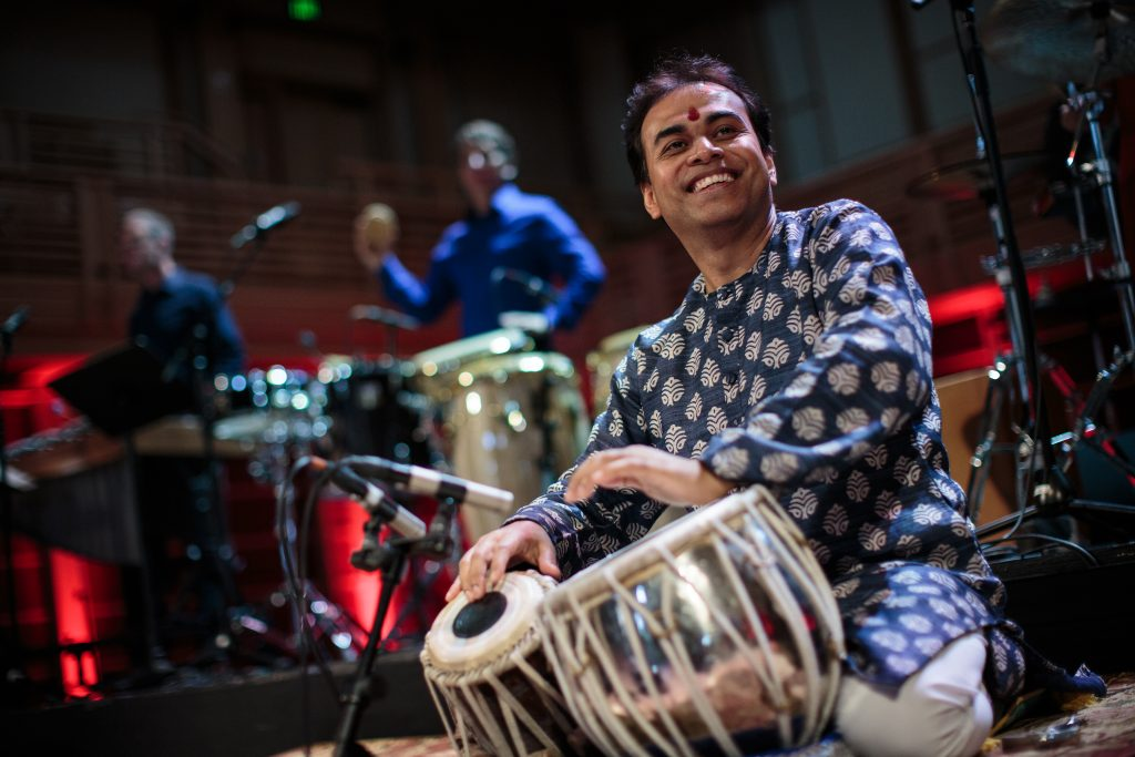 Sandeep Das plays the tabla, a short, squat drum, on stage at a concert.