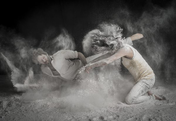 Two dancers, Tommy and Murielle, strike dramatic poses while all-purpose flour flies around them, creating a white, cloudy smoke.