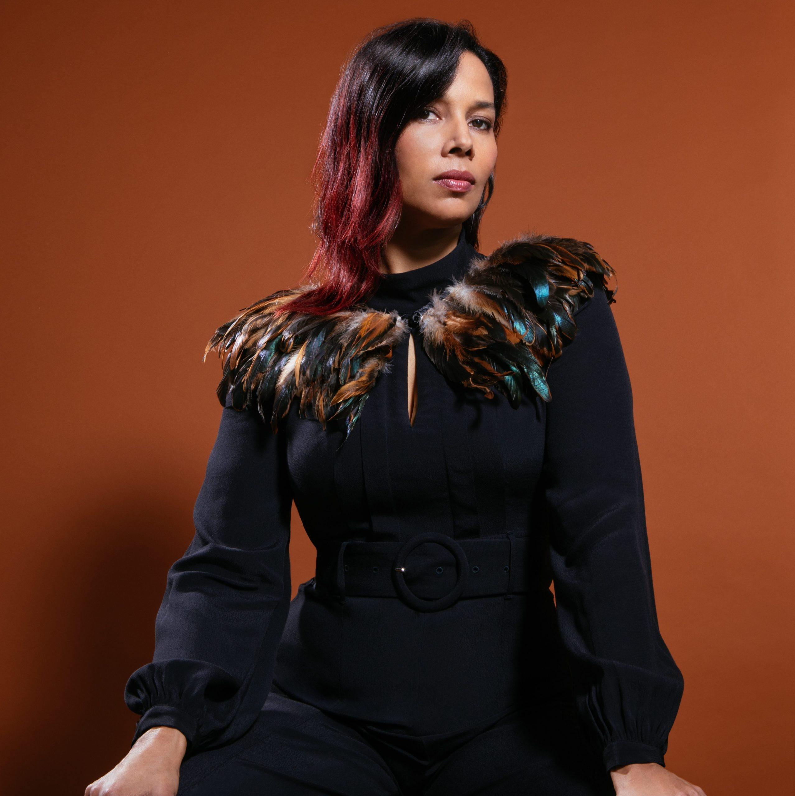 Artist Rhiannon Giddens poses wearing a black dress with feathers around the collar against a burnt orange background.