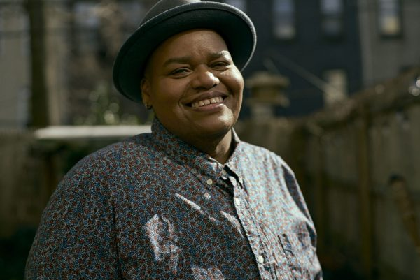 Artist Toshi Reagon wears a fedora and a button up shirt.
