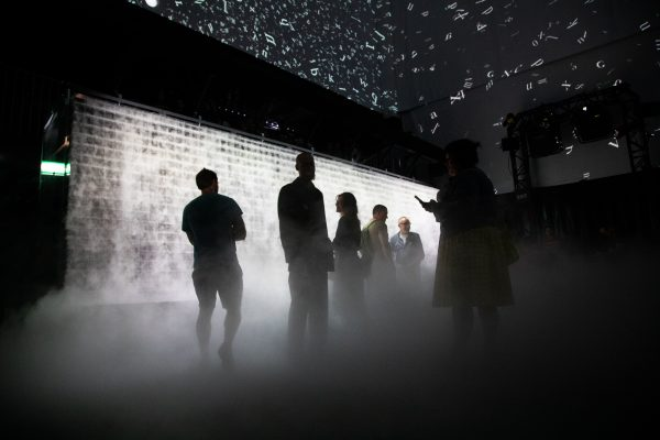 People stand in front of a large wall of smoke inside the Atmospheric Memory installation.