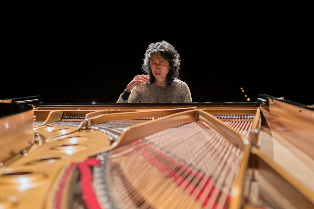 Pianist Mitsuko Uchida, a Japanese woman, sits at a piano. The piano's lid is open, revealing the strings connected to the keys.