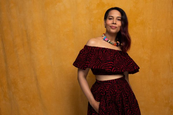 Artist Rhiannon Giddens leans up against a tan wall, wearing a two-piece dress and a beaded necklace.