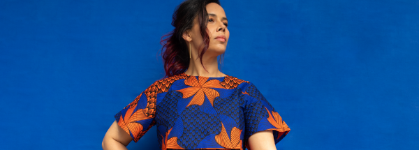 Rhiannon Giddens stands looking over her left shoulder wearing a colorful blue and orange dress.